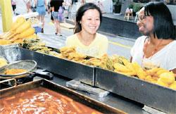 韓国語を勉強中の中国人(左)と英語講師として働く米国人が28日午後、ソウル弘益大学の前でトッポッキと練り物を食べている。
