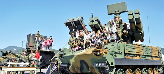 子どもがK-200装甲車に乗って記念撮影をしている。