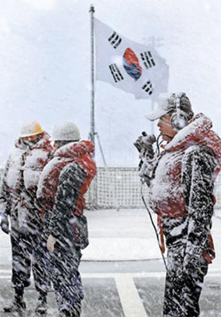 戦闘体系官ら(右側)と将兵が激しい吹雪の中で入港の準備している。