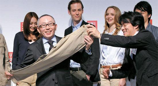 柳井正ユニクロ会長が東京で開かれた新商品発表会でズボンを手に持って見せている。