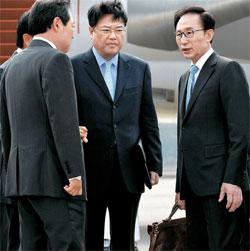 15日、右手にカバンを持ったままソウル空港に到着した李明博大統領(右)。