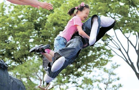 論介体験行事で子どもが倭将をかたどった人形を抱いて欄干から飛び降りている(写真=慶南道民日報)。