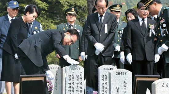 李明博(イ・ミョンバク)大統領が6日、国立ソウル顕忠院で、韓国戦争(1950-53)で戦死した故イ・チョンウ二等中士の納骨式を終えた後、墓碑を触っている。
