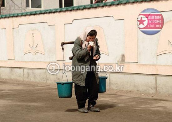 北朝鮮平壌市の最新式超高層アパートの住民は、毎日バケツを持って出勤する。