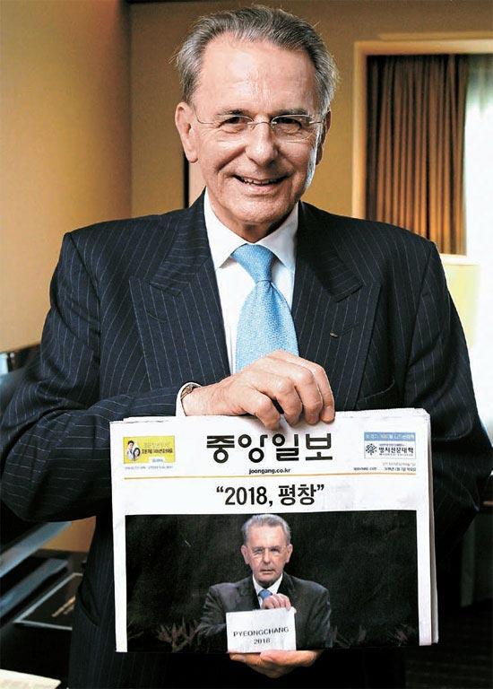 """ジャック・ロゲIOC委員長が、南アフリカ共和国のダーバンで開かれたIOCD総会で2018年冬季五輪開催地として""""平昌""""を発表する自身の様子が1面に掲載された中央日報の新聞を手に写真撮影した。彼は""""平昌""""を発表した6日(現地時間)の""""その時のその姿勢""""をそのまま取ってくれた。"""