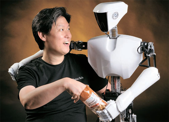 米バージニア工科大学のデニス・ホン教授が、今年のロボカップヒューマノイド(人間型ロボット)成人型部門で優勝した「チャーリ2」と肩を組みながらポップコーンを食べている。 「チャーリ2」は身長140センチのロボットで、 韓国作家オム・ユンソル氏が外観をデザインした (写真=バージニア工科大学ロメーラ研究所)。
