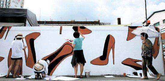 履き物をテーマに壁画を描く行事が18日、ソウル聖水洞(ソンスドン)で開かれた。行事に参加した靴デザイナー、ボランティアメンバー、区役所職員が長さ35メートルの壁に絵を描いている。