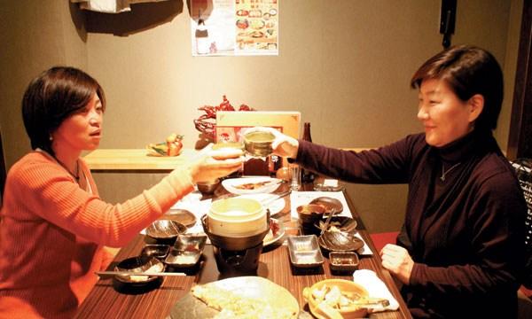 東京の韓国料理店で日本の女性がマッコリで乾杯している。