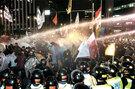 """""""半額授業料""""を求めてデモを行う学生に、警察が水鉄砲を発射している。"""