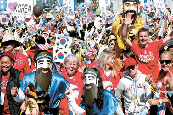 君(タングン、韓民族の始祖)に扮装した青年団員が外国人とともに「ハッピーバースデー」と大声で叫んでいる。
