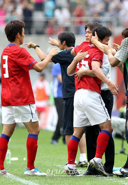 選手と抱擁しているオリンピック(五輪)サッカー代表チームの洪明甫(ホン・ミョンボ)監督(写真右側)。