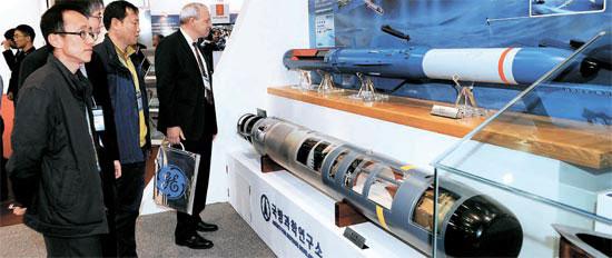 展示場を訪れた観覧客が垂直発射型対潜ミサイル「ホンサンオ(紅鮫)」「チョンサンオ(青鮫)」の模型を見ている。
