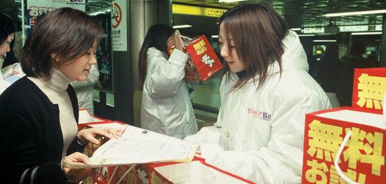 2001年、ヤフーBBの職員が東京地下鉄駅で超高速インターネットの販促を行っている(写真=ソフトバンク提供)。