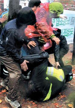 10日、ソウル汝矣島洞(ヨイドドン)産業銀行本店前で、韓米FTA阻止汎国民運動本部主管の「ハンナラ党の韓米FTA強行処理阻止決議大会」が開かれた。集会参加者を連行する途中に倒れたソウル警察庁のチョン・ジンウク警衛をデモ隊が蹴っている。