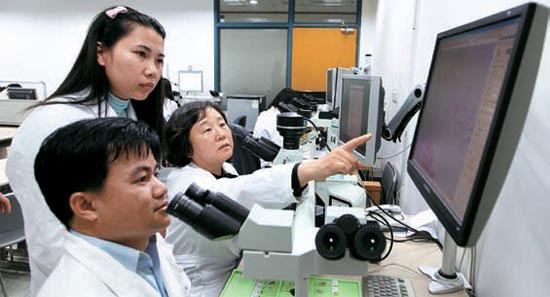 ラオス国立医大教授らがソウル大病院病理科のパク・インエ教授(左から3人目)から、顕微鏡に見える乳がん病理組織について説明を聞いている(写真=ソウル大病院提供)。