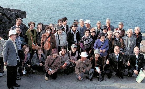 済州市龍譚洞(チェジュシ・ヨンダムドン)の龍頭(ヨンドゥ)岩を訪れた日本人団体観光客が27日、記念撮影をしている。日本農協の優秀組合員で、約1000人が30日まで済州を観光する(済州コンベンションビューロー提供)。