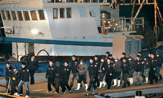 韓国海洋警察に拿捕された中国魯文漁15001号の船員が13日、仁川港海洋警察埠頭に到着し、仁川海洋警察署に連行されている。