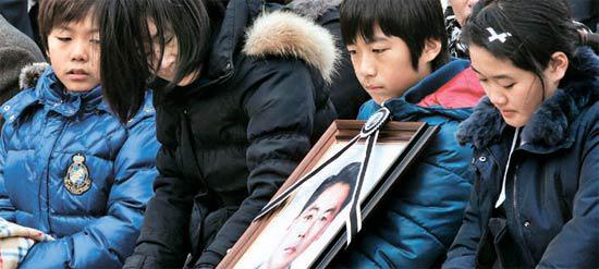 違法操業中の中国漁船を拿捕する過程で殉職した故イ・チョンホ警査の夫人ユン・ギョンミさん(左から2人目)が故人の遺影を見ている。左からイ警査の次男ミョンホン君、夫人ユンさん、長男ミョンフン君、長女ジウォンさん。