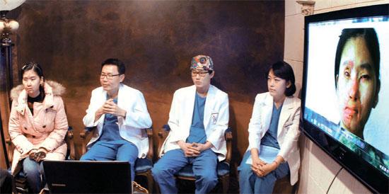 14日、ソウル江南区(カンナムグ)JK成形外科で、塩酸事故で顔に火傷を負ったマレーシア人女性タン・フィリンさん(左端)がチュ・グォン院長(左から2人目)ら医療陣と再建成形手術について相談している。