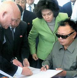 8月21日、金正日のロシア訪問当時に同行した金オク(写真の中で)。歓迎式場で、不自由な手で芳名録に署名する金正日をそばで補佐している。