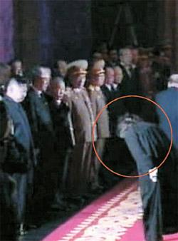 丸の中は、21日に錦繻山(クムスサン)記念宮殿で、金オクが金正日の遺体を参拝した後、金正恩に深く頭を下げる姿(写真=朝鮮中央テレビ)。