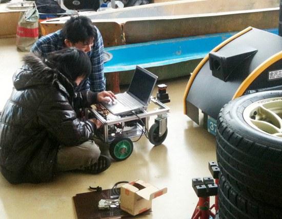 金沢工大の学生らが「夢の部屋」と呼ばれる夢考房実習室で太陽熱自動車作りの実習をしている。ここにはエンジニア20人が常駐して学生たちのプロジェクトを助けている。