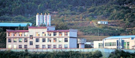 中国吉林省図們にある脱北者収容所「図們辺境管理所」。塀は鉄条網で囲まれ、2つの建物の間に監視塔が見える。脱北者のリュ・ソンジャさんが2002年に収容されたのは左側の建物。右側の建物は収容施設が狭くその後に新築された。図們収容所は北へ送還される脱北者を受け入れる所として知られる。