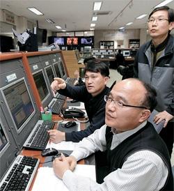 京畿道竜仁市のKT衛星管制センターで、イ・ジェヨル管制運用チーム長(前)と職員がムグンファ5号から送られてきた信号を分析している。 職員は英単語と数字が組み合わされた信号を読み取り、軌道修正など人工衛星に必要な措置を取る。