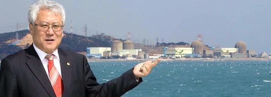 キム・スグン釜山(プサン)市議員が15日、釜山市機張郡(キジャングン)の海辺で、古里(コリ)原発事故防止対策について話している。後ろに古里原発1号機が見える。