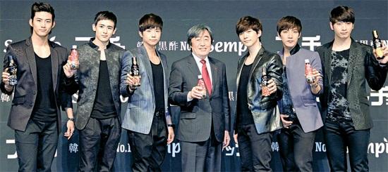 センピョ食品が黒酢飲料の日本市場広告モデルに起用した人気グループ2PMのメンバーが12日、日本・東京のホテルで開かれた新製品発表会で飲料を広報している。 真ん中は朴進善(パク・ジンソン)社長(写真=センピョ食品提供)。