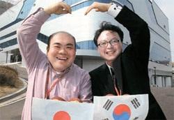 先月28日、日本ソフトバンクのハガワラ・ミノル氏(左)と韓国のKT-SBデータサービスのイ・ヨンギ・チーム長が金海(キムヘ)データバンク社屋の前で協力を強調するポーズを見せている。