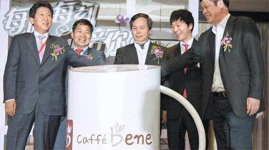 キム・ソングォン代表(右から2人目)とルチャンチン中企投資集団会長(真ん中)が27日、北京で開かれた「カフェベネ中国進出記念式」で契約記念ボタンを押している(写真=カフェベネ)。