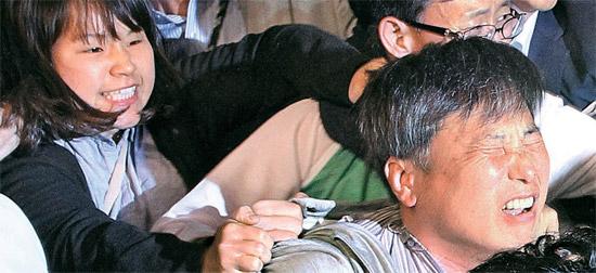 12日の統合進歩党中央委員会で主流派と見られる女性(左)が会議中に議長席に駆け上がり趙俊虎共同代表(右)の髪を後から引っ張っている。