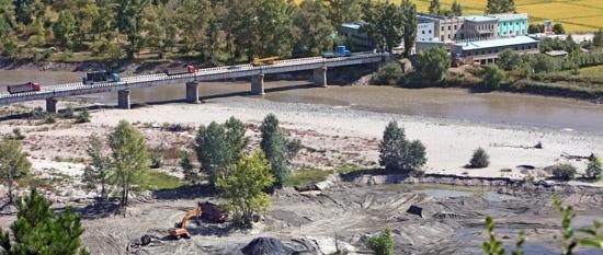 昨年9月、中国・吉林省延辺三合から眺めた豆満江(ドゥマンガン)と北朝鮮の風景。北朝鮮の最大鉄鉱石団地である茂山(ムサン)近隣の川底の砂には、鉱山から流れてきた鉄鉱成分が30%ほど含まれている。作業に動員されたパワーショベルが川底の砂を集めている。会寧(フェリョン)税関の橋で北朝鮮に向かう中国の貨物車が手続きを待っている。