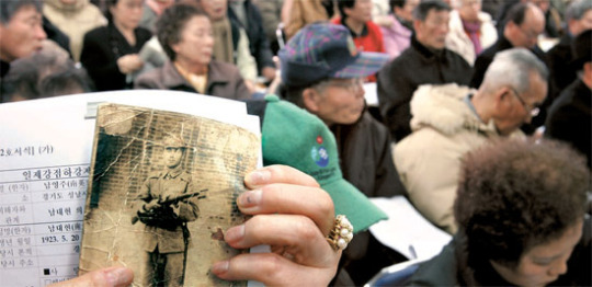 国務総理室傘下の日帝強占下強制動員被害真相究明委員会が05年2-6月、強制動員被害申告を受け付けた。受付初日の05年2月1日、ソウル鍾路区の真相究明委を訪れた遺族が、日本軍に徴兵されて戦死した父の写真を見せている。[中央フォト]