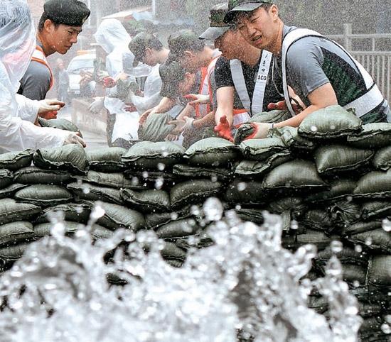 30日、官民軍合同防災訓練がソウル牛眠洞(ウミョンドン)ヒョンチョン村で行われ、軍将兵が雨水流入状況を想定して土嚢を積み上げている。