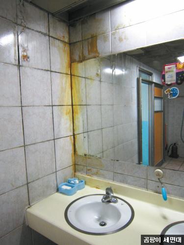ソウル・江南のある小学校のトイレの洗面台。鏡と壁の間にかびとシリコンなどがこびりついている。