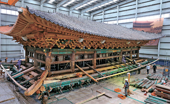 5日、崇礼門復元現場で関係者らが1階屋根の軒や垂木および丹青工事をしている。