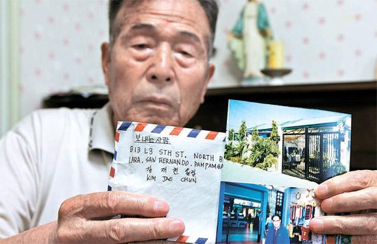 キム・ジャヒョンさんが16日、京畿道水原市(キョンギド・スウォンシ)の自宅で息子のキム・ジェチョンさんが生前に送った国際郵便の封筒と現地の写真を見せている。息子は昨年フィリピンで失踪し最近になり殺害されたと明らかになった。