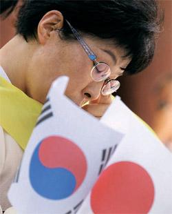 14日、ソウル・タプコル公園の前で「韓日の歴史を克服し友好を推進する会」のメンバーが日本軍慰安婦問題に謝罪を促す集会の途中で涙を流している。