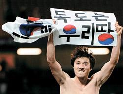 韓国の五輪サッカー3位が決まった後、「独島はわれわれの領土」と書かれた紙を持ってパフォーマンスをした朴種佑(パク・ジョンウ)(写真=中央フォト)。