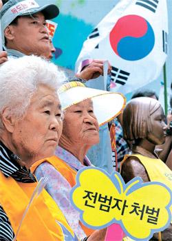 29日、ソウル中学洞(チュンハクトン)日本大使館の前で、「日本軍慰安婦問題解決のための定期水曜デモ」が開かれた。慰安婦被害者のイ・オクソンさん、パク・オクソンさん(左から)が「戦犯処罰」と書かれたプラカードを持っている。