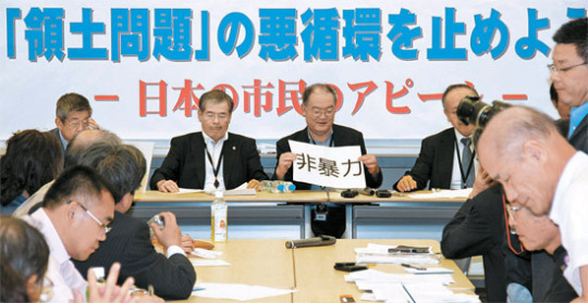 日本の知識人と市民団体代表が28日、東京の参議院議員会館で記者会見を行い、「非暴力」と書かれた紙を見せている。