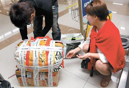 2日、金浦(キンポ)空港の大韓航空カウンターの前で、日本人観光客がビニールテープを使って2つの荷物を一つにくくっている。大韓航空が今月から国際線の荷物制限を変更したからだ。超過する荷物の個数によっても料金が追加請求されるため、その場で荷物を一つにくくり付ける姿が見られた。