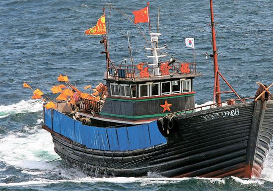 """先月違法操業した中国""""鉄甲船""""=先月24日、済州市遮帰島の西側140キロメートル海上、韓国側EEZより29キロメートル内側で、高さ約1.5メートルの鉄板を装備し、1.6メートルの串20本余りを設置した中国漁船が済州海洋警察の検問に応じず逃走している。この日済州海域に現れた中国漁船10隻余りはすべて海洋警察の取り締まりを妨害するために鉄串と鉄板を設置していた。韓国領海で操業する多くの蚒国漁船は16日に公開されたこの写真の漁船のように太極旗を付けている(写真=済州海洋警察)。"""