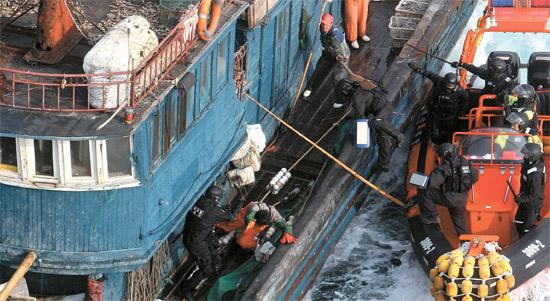 竹の棒を振り回す中国船員=昨年11月、於青島沖海上で海洋警察による違法操業の取り締まりに中国船員が竹の棒を振り回し抵抗している。