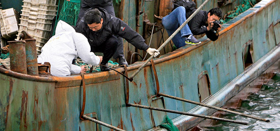 木浦海洋警察捜査官が17日、全羅南道木浦海洋警察の専用埠頭で、韓国海洋警察の取り締まり船の接近を防ぐために設置された中国漁船の鉄の棒を調べている。