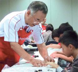 先月13日、愛知県長久手市で開かれたトヨタの「科学のびっくり箱!」授業で、講師のサトウ・シゲアキさん(59)が小学生にホバークラフト模型の製作方法を教えている。