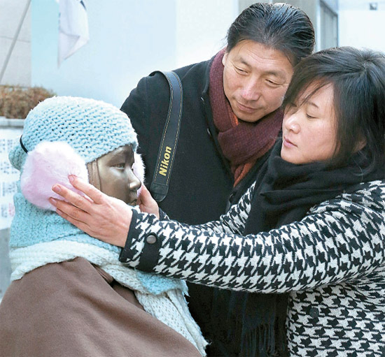 キム・ウンソン氏(左)とキム・ソギョン氏の夫婦が20日、市民が少女像にかぶせた耳当てを整えている。