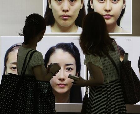 整形手術の広告を見ている女性(写真は資料)。